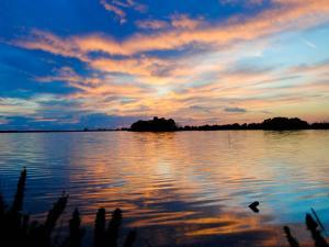 foto di tramonto tramonto Riflessi e sfumature sul lago di Fogliano al tramonto